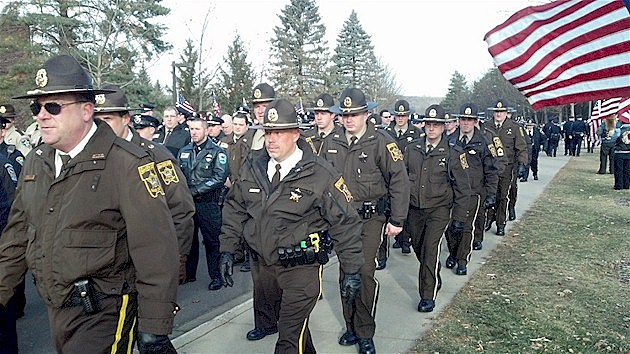 Law enforcement officers walking together to the funeral of Cold Spring Officer Tom Decker