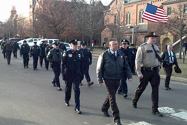 Police officers walking together to the funeral of Officer Tom Decker.