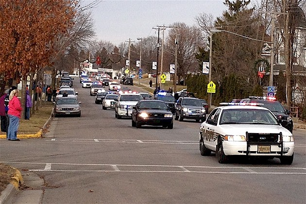 Law enforcement travel in a procession through Cold Spring on their way to the burial of Officer Tom Decker