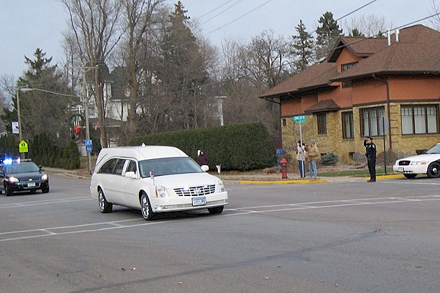 A policeman salutes the hearse carrying Officer Tom Decker on Red River Avenue in Cold Spring to the St. Nicholas Catholic Cemetery.