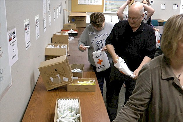 """Electrolux volunteers pack """"comfort kits"""" for the Red Cross."""