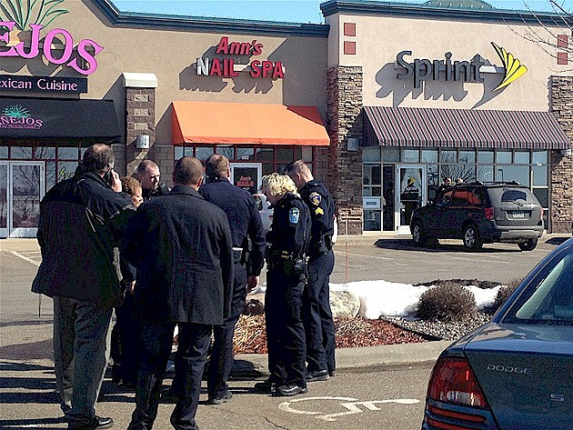 Police confer outside the Sprint Store in Sartell, the scene of what is believed to be a shooting just before noon, March 13, 2014.