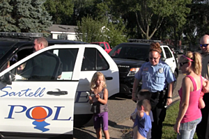 Sartell Police officers interact with kids during National Night Out. (Photo: Alex Svejkovsky, WJON)