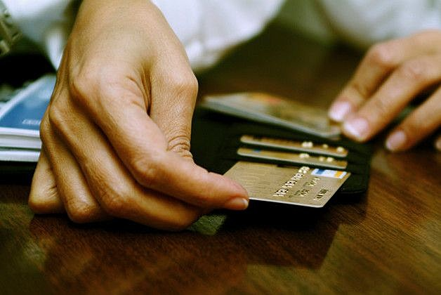 Person's hand taking out a credit card from a wallet