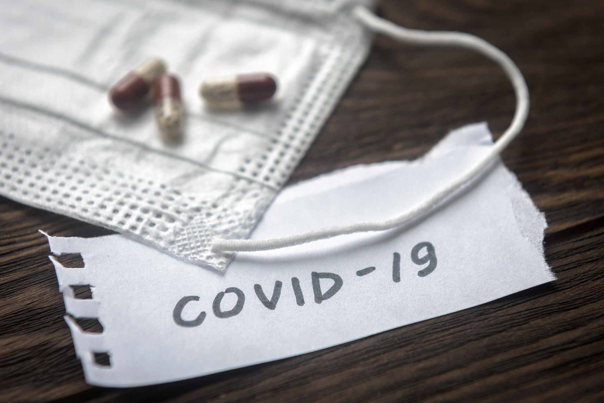 Coronavirus concept. Note COVID-19, Protective medical mask and pill capsules for treatment coronavirus. Novel corona virus outbreak.